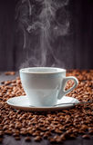 Hot aromatic coffee drink in the white cup with beans background Stock Photo