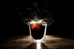 Hot and aromatic coffee spilling from transparent glass cup. Located on the wooden table on the dark background Stock Images