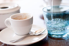 Hot aromatic espresso cup and cold water in glass Royalty Free Stock Images