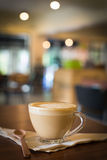 Hot art Latte Coffee in a cup on wooden table and Coffee shop bl Royalty Free Stock Photos
