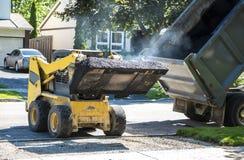 Hot Asphalt. A little truck transferring hot asphalt from a big truck to a driveway stock photo