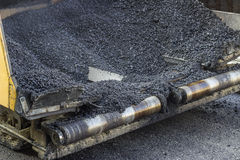 Hot asphalt in paver machine Stock Photos