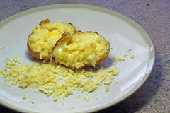 Hot baked jacket potato with melted cheese. Royalty Free Stock Photography