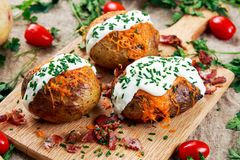 Hot Baked Potato with cheese, bacon, chives and sour cream. On cutting board stock photos