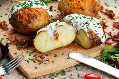 Hot Baked Potato with cheese, bacon, chives and sour cream. Royalty Free Stock Images