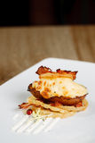 Hot Baked Potato with cheese and bacon. Hot rustic potato skins with cheese and bacon close-up on the table, vertical royalty free stock photos