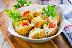 Hot Baked potato with vegetables and sour cream. Royalty Free Stock Image