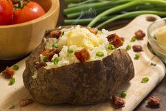 Hot baked potatoe. Fresh hot baked potato with butter bacon and chives on a cutting board royalty free stock images