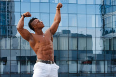 Hot Beautiful black guy with bulging muscles posing against the backdrop of the urban landscape Man fitness. Stock Photos