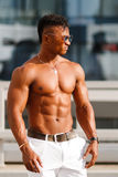 Hot Beautiful black guy with bulging muscles posing against the backdrop of the urban landscape. Man fitness model with a beautifu Royalty Free Stock Photography