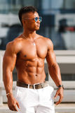 Hot Beautiful black guy with bulging muscles posing against the backdrop of the urban landscape. Man fitness model Royalty Free Stock Photo