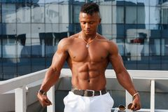 Hot Beautiful black guy with bulging muscles posing against the backdrop of the urban landscape. Man fitness model. Royalty Free Stock Photos