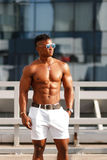 Hot Beautiful black guy with bulging muscles posing against the backdrop of the urban landscape. Man fitness model. Stock Photos