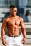 Hot Beautiful black guy with bulging muscles posing against the backdrop of the urban landscape. Man fitness model Stock Photos
