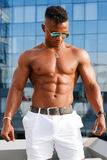 Hot Beautiful black guy with bulging muscles posing against the backdrop of the urban landscape. Man fitness model. Stock Image