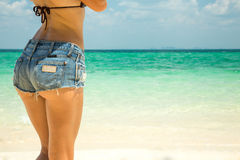 Hot beautiful woman in denim shorts. On sea background Royalty Free Stock Photos
