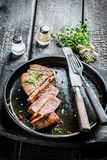 Hot beef with rosemary and papper ready to eat. On burnt table Stock Photos