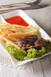 Hot beef steak with french fries and ketchup close-up. vertical. Hot beef steak with french fries and ketchup on a white plate on the table close-up. vertical Stock Photography