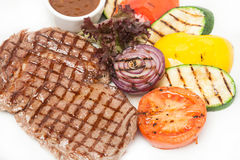 Hot beef steak with garnish of grilled color fresh vegetable Royalty Free Stock Photos