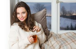 Hot beverage for cold days. Gorgeous young brunette woman holding cup of hot beverage stock photos
