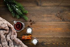 Hot beverage for warm winter evening. Mulled wine near cinnamon, fir branches, wool blanket, candles on dark wooden. Wooden background top view royalty free stock photos