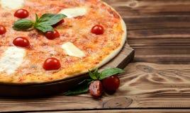 Hot big margarita pizza with mozzarella melting cheese bacon tomatoes Royalty Free Stock Photo