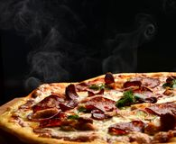 Hot big pepperoni pizza tasty pizza composition with melting cheese bacon tomatoes ham paprika steam smoke. On black background Stock Photo