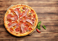 Hot big whole tasty pizza with melting cheese bacon tomatoes ham. Paprika on a rustic wooden table and copy text space Stock Image