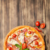 Hot big whole tasty pizza with melting cheese bacon tomatoes ham Stock Photography