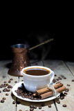 Hot Black Coffee with Coffee Beans, Cinnamon and Coffee Pot on Wooden Table Stock Photo