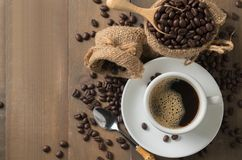 Hot black coffee on cup and roasted coffee beans in wood scoop o royalty free stock photo