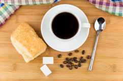 Hot black coffee, flaky biscuits and sugar cubes on table Stock Photo