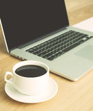 Hot coffee with laptop on wood table. Hot black coffee with laptop and white paper royalty free stock image