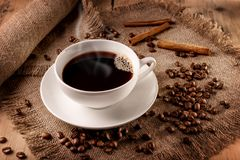 Hot black coffee. Natural hot black coffee in a white cup on a sackcloth napkin Stock Images