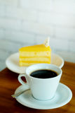 Hot black coffee and Orange cake on wooden table and white brick wall Stock Image