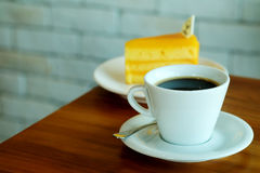 Hot black coffee and Orange cake on wooden table and white brick wall Stock Photo