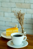 Hot black coffee and Orange cake on wooden table and white brick wall Royalty Free Stock Image