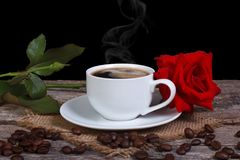 Hot black coffee and red rose on a wooden table Royalty Free Stock Image