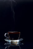 Hot black coffee in a transparent glass cup on a black background Stock Photos