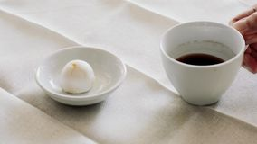 Hot of black coffee in white ceramic cup and eatting small white moon cake in plate on table. Drink a hot of black coffee in white ceramic cup and eatting small stock footage