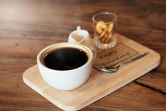 Hot black coffee in white cup Served with mini biscuit on rough wooden plate Royalty Free Stock Images