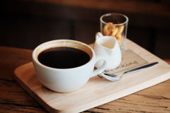 Hot black coffee in white cup Served with mini biscuit on rough wooden plate Royalty Free Stock Photo