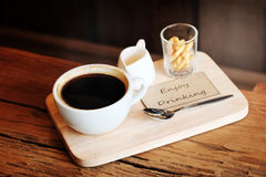 Hot black coffee in white cup Served with mini biscuit on rough wooden plate Stock Images