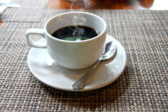 Hot Black coffee in a white cup on the table and have smoke comi Royalty Free Stock Photo