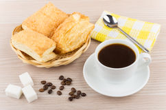Hot black coffee, wicker basket with flaky biscuits, sugar cubes Stock Photo