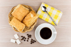Hot black coffee, wicker basket with flaky biscuits, sugar cubes Stock Photos