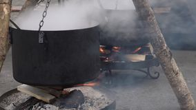 Hot black smoking pot on fire boiling water, preparing soup or tea in a city fair. Burning firewood under big pot in a camp.  stock footage