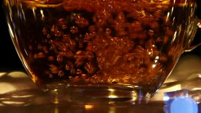 Hot black tea being poured into glass cup. Slow motion. Hot black tea being poured into glass cup, transparent mug begins to sweat and stands on saucer, light stock footage