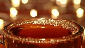 Hot black tea being poured into glass transparent cup, closeups stock video