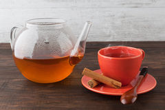 Hot black tea in cup and teapot with cinnamon sticks. Hot black tea in red teacup and teapot with cinnamon sticks and wooden spoon Royalty Free Stock Images
